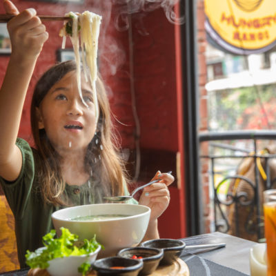Vietnam Hanoi Hungry Hanoi Restaurant Girl Eating Pho Noodle Soup Credit G Adventures